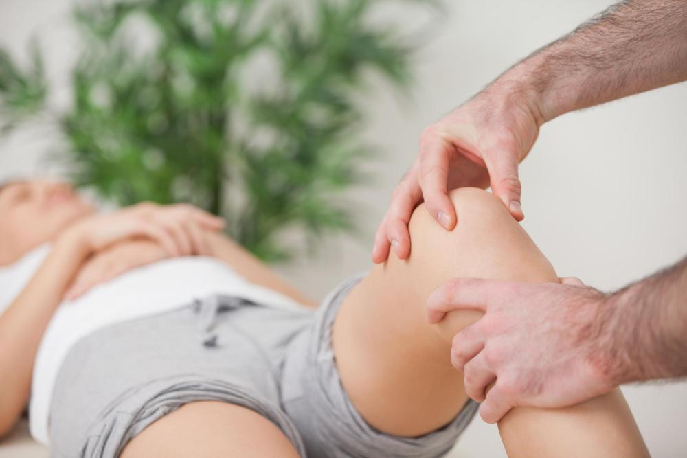 Woman receiving knee pain relief from chiropractor.