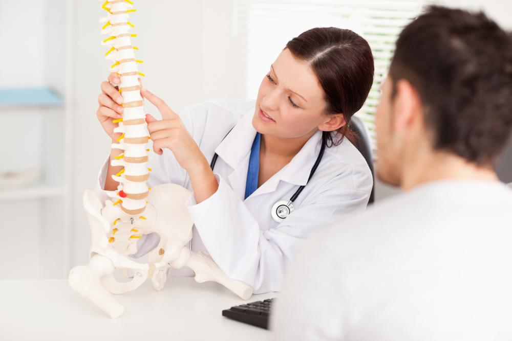 Chiropractor talking about pain management with a client.